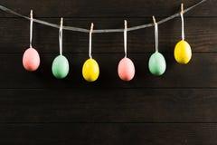 在绳索的复活节五颜六色的虚幻的鸡蛋有木背景 与拷贝空间的黑暗的照片 免版税库存照片