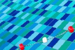 在绳索的红色和白色塑料浮游物在水池 库存图片