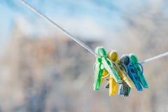 在绳索的绿色,黄色和蓝色晒衣夹,报道用冬天树冰 图库摄影