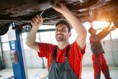 在维护修理服务站的Profecional汽车修理师改变的机油 库存照片