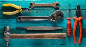 在绿松石木背景的工具:螺丝刀,钳子,小块,锤子,少年,文件,可调扳手 免版税图库摄影