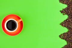 在绿皮书的形式之字形烤咖啡豆计划的全部在充分的陶瓷杯子无奶咖啡旁边 免版税库存照片