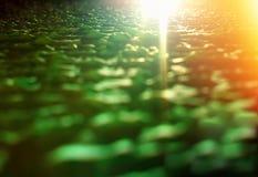 在绿色七高八低的表面纹理背景hd的橙色光泄漏 库存图片