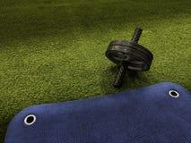 在绿色人为草和蓝色训练席子的吸收轮子 库存照片
