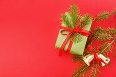 在绿色包装纸, xmas响铃,在红色背景的杉木的礼物盒 复制空间 库存图片