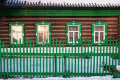在绿色原木小屋门面的正面图在冬天 图库摄影