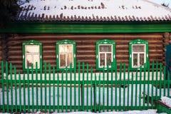 在绿色原木小屋门面的正面图在冬天 免版税库存照片
