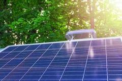 在绿色叶子和阳光背景的太阳电池板  概念可再造能源,环境保护,环境关心 库存照片