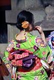 在绿色和服礼服的妇女和在日本寺庙的深桃红色的框格后 免版税图库摄影