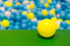 在绿色地板上的黄色球在一个球坑在学校操场 免版税库存图片