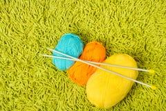 在绿色地毯的编织的纱线球和针 免版税库存照片