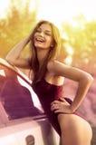 在绿色域的性感的妇女和汽车 免版税库存图片