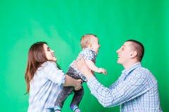 在绿色墙壁的年轻家庭乐趣 免版税库存照片