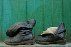 在绿色墙壁附近的两只老黑皮靴 免版税库存照片