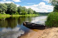 在绿色夏天海滩的老划艇在与白色的蓝天下 库存图片
