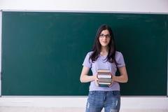 在绿色委员会前面的年轻女老师学生 免版税库存照片