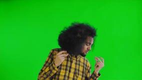 在绿色屏幕或色度关键背景上的喜悦的微笑的年轻人非洲人跳舞 r 影视素材