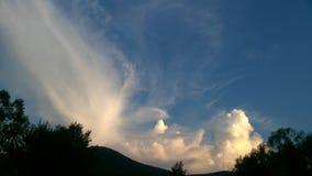 在绿色山的白色积云 库存图片