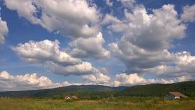 在绿色山的白色积云 免版税库存照片