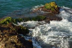 在绿色岩石岸和泡沫附近的美好的海波浪背景 库存照片