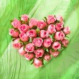在绿色布料的粉红色玫瑰色重点 免版税库存图片