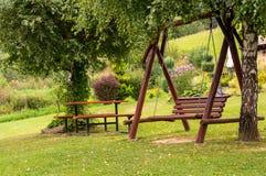 在绿色庭院的一条垂悬的长凳 免版税图库摄影