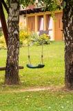 在绿色庭院的一条垂悬的长凳 库存照片