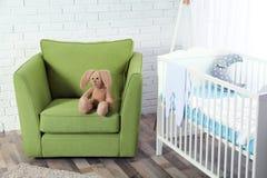 在绿色扶手椅子的逗人喜爱的兔宝宝玩具 库存图片