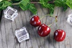 在绿色旁边的樱桃和在葡萄酒木桌上的冰块 免版税库存图片