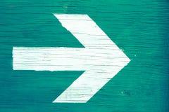 在绿色木头的手动地被绘的箭头 图库摄影