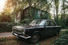在绿色木老房子背景的年迈的葡萄酒苏联黑减速火箭的汽车  免版税库存图片