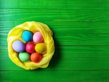 在绿色木背景的多彩多姿的复活节彩蛋 库存图片