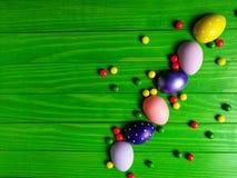 在绿色木背景的多彩多姿的复活节彩蛋 免版税库存照片