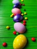 在绿色木背景的多彩多姿的复活节彩蛋 库存照片