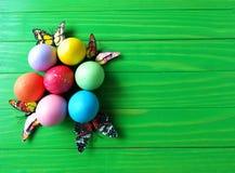 在绿色木背景的多彩多姿的复活节彩蛋 图库摄影