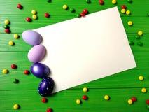 在绿色木背景的多彩多姿的复活节彩蛋 免版税图库摄影
