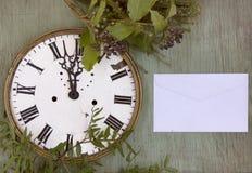 在绿色木背景的老时钟 与植物和紫色莓果的新年背景 新鲜的叶子和紫色莓果 Vinta 免版税库存图片