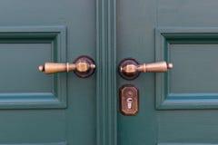 在绿色木门的金黄门把手 老门把手 库存图片