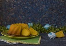 在绿色板材的复活节面包和绘了复活节彩蛋离子黑暗的石桌用绿草装饰 免版税图库摄影