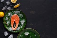 在绿色板材的新鲜的三文鱼在黑暗的背景 免版税图库摄影