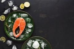 在绿色板材的新鲜的三文鱼在黑暗的背景 库存照片