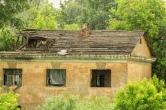 在绿色树中的老被破坏的房子 免版税图库摄影