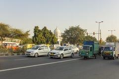 在绿色树背景和白色寺庙的圆顶的印度城市交通 库存图片