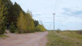 在绿色森林和输电线之间的乡下公路在夏天调遣 股票视频