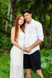 在绿色森林背景的年轻夫妇  免版税图库摄影
