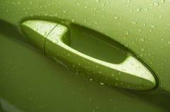 在绿色汽车把柄的雨珠  免版税库存图片
