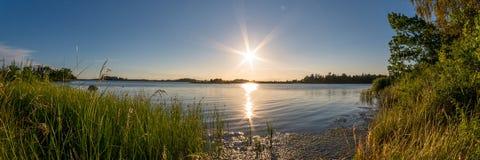 在绿色海洋海岸全景的美好的日落 免版税库存图片