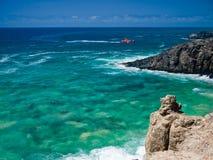 在绿色海浪的红色海岸警卫队小船 库存照片