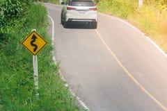 在绿色灌木的黄色交通标志`迷宫交通`在路旁边有汽车和阳光背景 库存照片