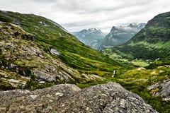 在绿色牧场地的道路西挪威山的有雪的在山顶和黑暗的多云天空 免版税图库摄影